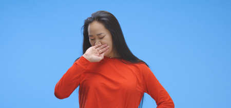 Medium shot of young woman yawning against blue background