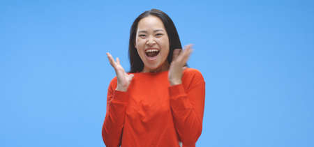 Medium shot of young woman getting excited against blue background