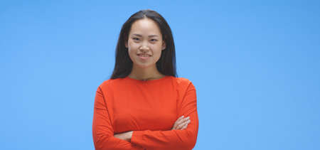 Medium shot of young woman staring with friendly smile against blue background