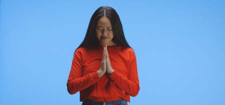 Medium shot of a young woman praying in front of the camera Imagens