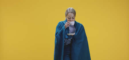 Medium shot of a sick woman enjoying a cup of tea