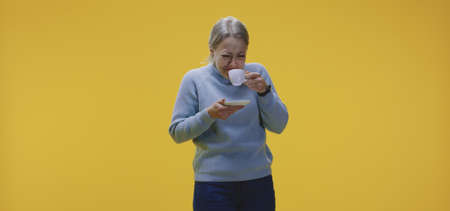 Medium shot of a young woman tasting coffee against yellow background Zdjęcie Seryjne