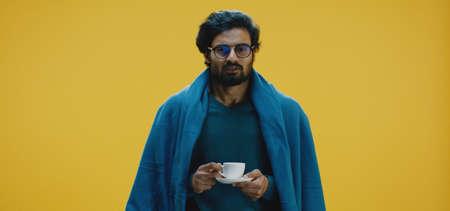 Medium shot of a sick man drinking a cup of tea