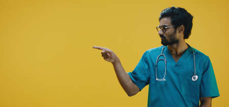 Medium shot of young doctor pointing against yellow background Banco de Imagens