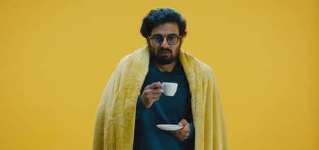 Medium shot of a sick man enjoying a cup of tea