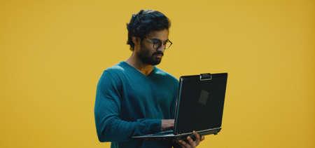 Medium shot of young man typing on his laptop