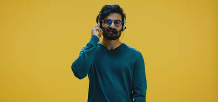 Medium shot of young man talking white wearing headset Banco de Imagens