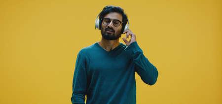 Medium shot of young man listening music through headphones Banco de Imagens - 137938559