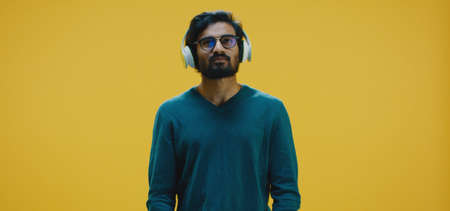 Medium shot of young man listening music through headphones Banco de Imagens - 137938560