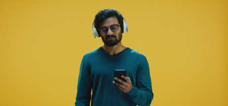 Medium shot of young man listening music from smartphone through headphones