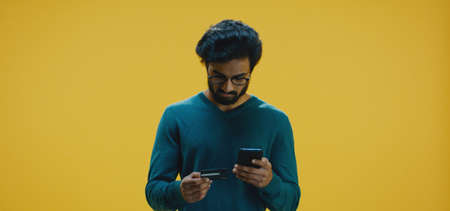 Medium shot of young man paying with credit card on a smartphone