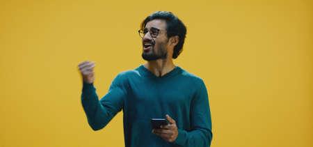 Medium shot of young man texting on smartphone Banco de Imagens