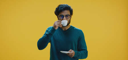 Medium shot of young man drinking bad coffee