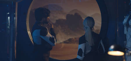 Medium shot of a male and a female astronaut talking while standing by Martian base window