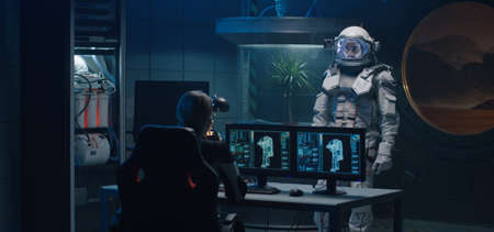 Medium shot of a female astronaut helping her comrade to turn on lamps and camera on his spacesuit Imagens