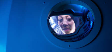Medium shot of a female astronaut looking out of porthole of a spaceship