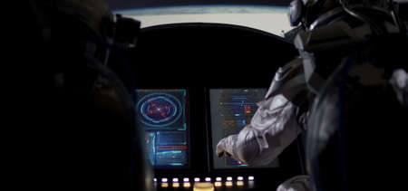 Medium shot of two astronauts using control panel while orbiting around a planet in a spaceship