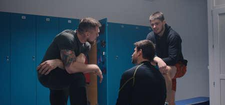 Medium shot of two men bullying their peer in locker room