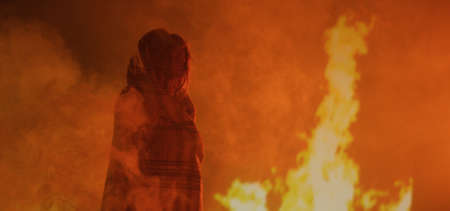 Medium shot of a girl crying while being surrounded by flames