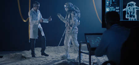 Full shot of an astronaut and scientists testing mobility of a spacesuit with dancing