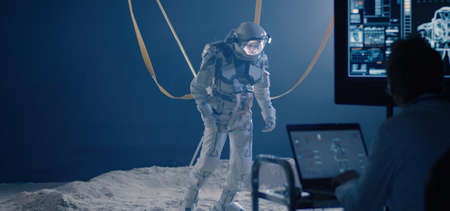 Medium shot of an astronaut and scientists testing mobility of a spacesuit