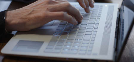 Close-up of a man typing on a laptop keyboard Foto de archivo