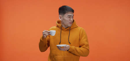 Medium shot of young man tasting tea against orange background