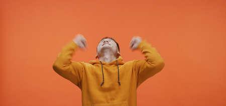 Medium shot of young man cheering against orange background Imagens
