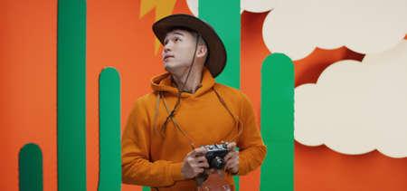 Medium shot of young man taking photos against orange background