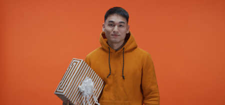 Medium shot of young man catching box against orange background