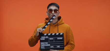 Medium shot of young man standing with clapperboard against orange background Imagens