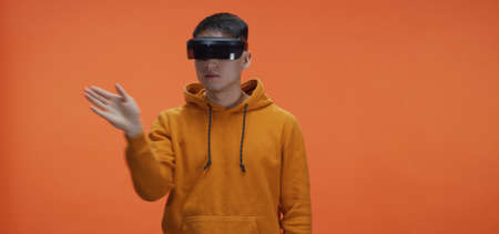 Medium shot of young man using vr goggles and doing hand gestures against orange background
