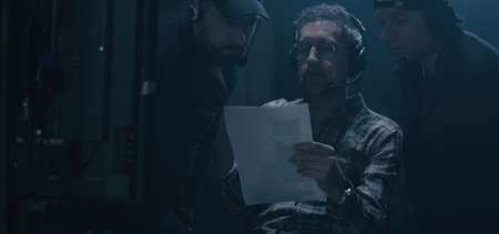 Medium shot of a director discussing an issue with a technician before a monitor