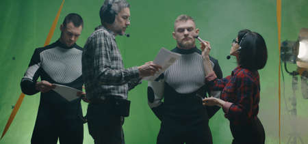 Medium shot of a cosmetician preparing an actor while others discussing over the script before shooting a scene Standard-Bild