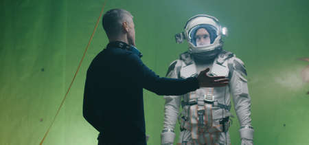 Medium shot of a director holding the script and arguing with crew members before a shoot