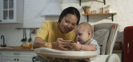 Medium close-up of a young father showing smartphone to his baby