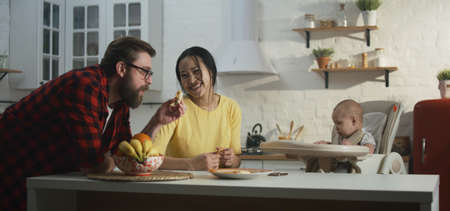 Medium shot of a cheerful young couple having breakfast with their baby in the kitchen