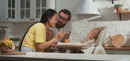Medium shot of a young mother and father feeding their baby in the kitchen
