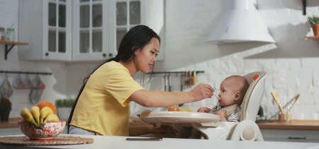 Medium shot of a cheerful young couple feeding their baby in the kitchen