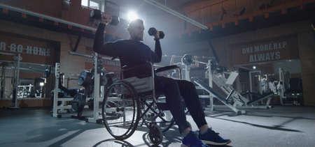 Medium shot of wheelchair man lifting weight in gym