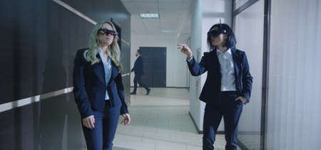 Medium shot of businesswomen using VR glasses and walking in office corridor