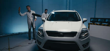 Full shot of engineers working in test chamber on a car