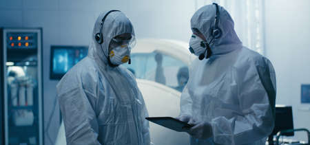 Medium shot of engineers discussing in clean room