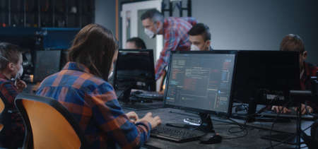 Medium shot of a girl in face mask learning programming in school Reklamní fotografie