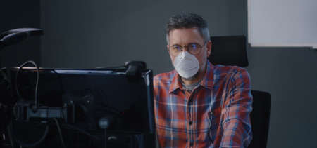 Medium shot of a face mask wearing man having a video call