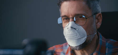Close-up of a face mask wearing man having a video call