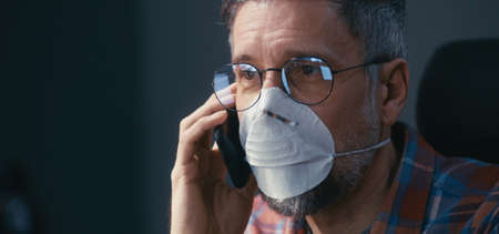 Close-up of a face mask wearing man having a phone call