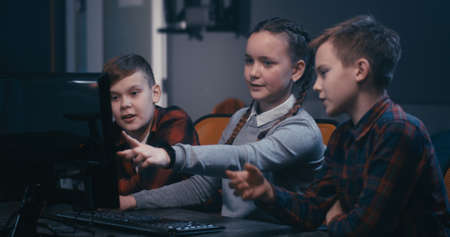 Medium shot of programmer students brainstorming while sitting at a computer in a class Reklamní fotografie