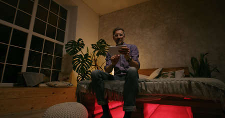 Full shot of a man sitting on his bed and turning on flashing light effects while listening to music