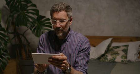 Medium shot of a man switching lighting on and off with home hub in a smart home